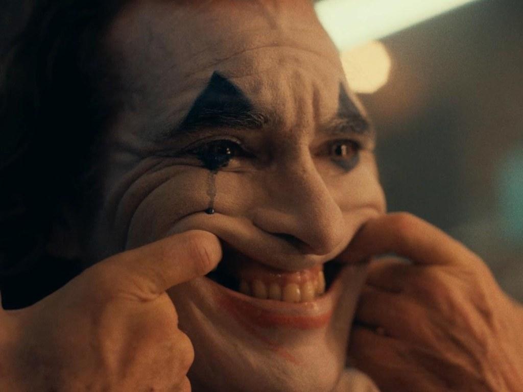 PArmaklarını ağzına sokarak kendini zorla gülümseten joker